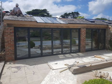 grey-bifold=doors out onto a swimming pool